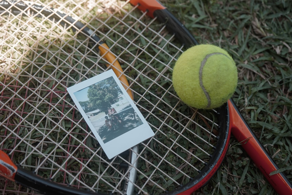 green tennis ball beside white and black card